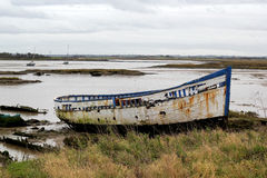 An old boat on the sand on the side of an estuary Stock Photography