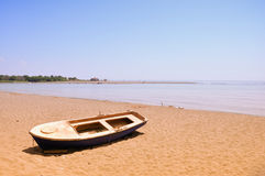 Old boat on sandy beach. With blue sky and beautiful sea Royalty Free Stock Image