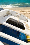 Old boat on a sandy beach. Old abandoned blue and white colored boat on a sandy beach Stock Photo