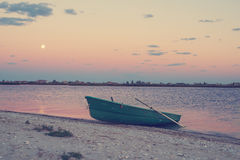 Old boat on sea coast during rising moon Stock Photography
