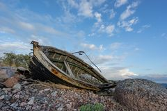 Old boat, shore and evening light Royalty Free Stock Images