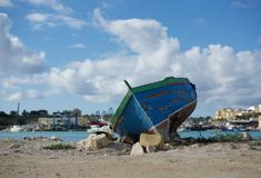 Old boat on the shore with Marsaxlokk village Malta background, traditional old maltese boat on the coast, boat ruins Stock Images