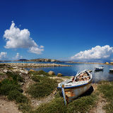 Old Boat on the Shore of the Mediterranean. Old, worn out boat on the shore of bright blue water with blue sky and fluffy clouds. The shoreline pictured is the stock photo