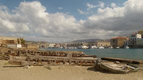 Old boat sprawling and gangway lying on the sand against the background of the promenade of Chania stock photography