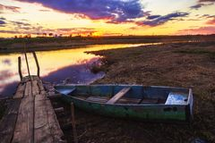 Old boat and sunset on the river Royalty Free Stock Images