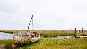 Old boat. Thornham harbour with old wooden clinker built boat on the marsh stock photo