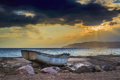 Old Boat thrown by storm on the beach Stock Photo