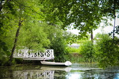 Old boat in the trees at the pier. Green trees overhang and create shade and comfort Royalty Free Stock Image