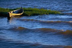 Old boat on water. Old wooden boat on blue water Royalty Free Stock Image