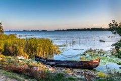 Old boat on the water in the lake among the reeds. Bright and ca Royalty Free Stock Photos