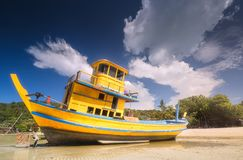 Old boat on white beach Phi Phi Island, Thailand. Tropical seascape with old and broken boat that ran aground on white beach of Phi Phi Island, Thailand Stock Image