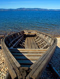 Old boat. Wooden boat on the lake  on a background of blue sky and water Stock Images