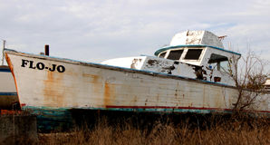 Old Boat. An old wooden sport fishing boat slowly decays in the graveyard of anglers` dreams Stock Photo