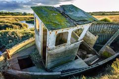 Old boat wreck abandoned in marshland royalty free stock images