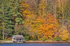 Old boathouse on lake in colorful autumn Stock Images
