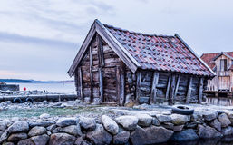 Old boathouse. An old wooden boathouse on a pier of stones still standing after years and years of bad weather on the Norwegian westcoast Stock Photo