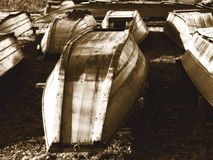 Old Boats. A bunch of old river boats laying upside-down on a grass field, in sepia tone and increased white glow for more impact Stock Photography