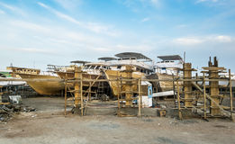 Old boats are being repaired on the shore at the port Stock Image