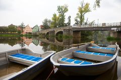 Old Boats On A River. These boats invites for a tour on the river. The bridge in the back is from the 16th century. The water reflects the houses and the trees Stock Image