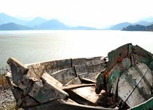 Old boats on the shores of the lake   in the background of the mountain stock photo