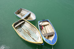 Old boats. Three old row boats floating around in the sea Stock Photography