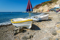 Old boats and umbrella on the beach of Santorini island Stock Photos