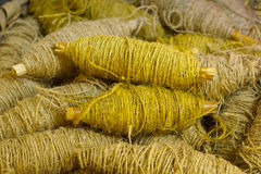 Old bobbin with yellow jute rope Stock Photo