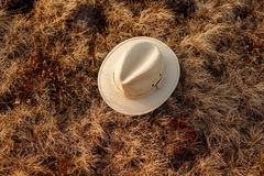 Old boho or cowboy hat on grass at sunset in mountains, travel c royalty free stock photography