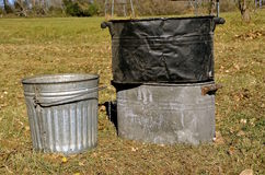 Old boilers and garbage can pail. Several old boilers and a half sized metal garbage can stock photography