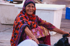 Old and Bold. Old lady from fishermen community of Muscat awaiting the fishing bots to dock Muscat, Oman Royalty Free Stock Images