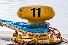 Old bollard with the rope. Old bollard with line in harbor stock image