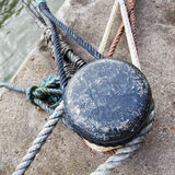 Old bollard at the pier. With ropes of anchored ships royalty free stock photography
