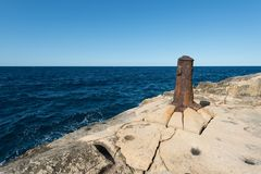 Old bollard on rocky coast Stock Images