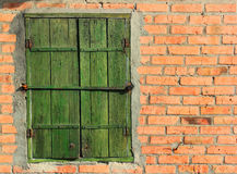 Old bolted wooden window shutters on red brick wall Royalty Free Stock Photography