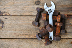 Old bolts with adjustable wrench tools on wooden background Stock Image