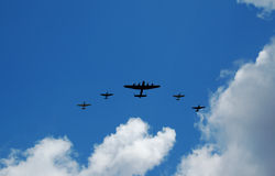 Old bomber and fighter planes. An old bomber and four fighter planes in a blue cloudy sky Stock Photos
