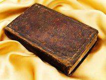 Old book. Old closed book at the golden fabric drapery Stock Photo