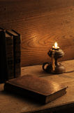 Old book. On a wooden table by candlelight royalty free stock photography