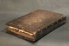 Old book. Old brown leather  book lying on the grey background Stock Photo
