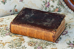 Old book. Old leather bound book on antique chair Stock Photo