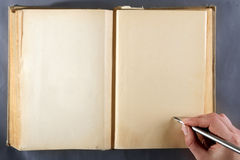 Old book. Old note-book and the hand with pen on it Royalty Free Stock Photo
