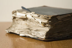 Old book. An large, ragged, old book on a wooden table Royalty Free Stock Images