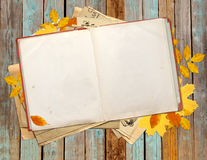 Old book and autumn leaves on wooden boards Royalty Free Stock Image