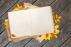 Old book and autumn leaves on wooden boards Royalty Free Stock Photography