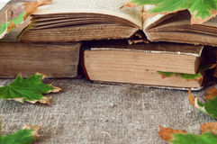 Old book with autumn maple leaves Stock Photos