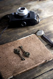 Old book and a brass key on a vintage surface Royalty Free Stock Photos
