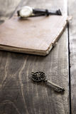 Old book and a brass key on a vintage surface Stock Photos