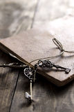 Old book and a brass key on a vintage surface Stock Photo