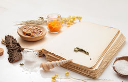 Old book and a bunch of dried herbs on white background Royalty Free Stock Photo