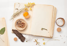 Old book and a bunch of dried herbs on white background Stock Photo